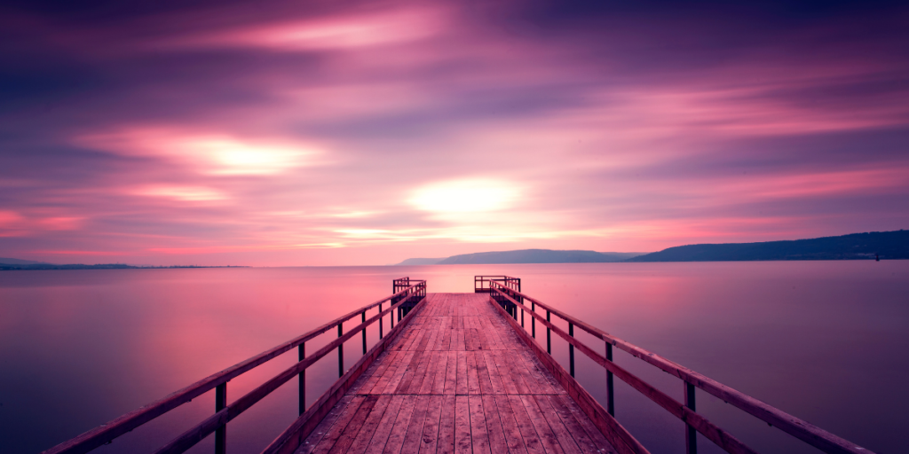 a wooden dock stretches out into water under a purple sky