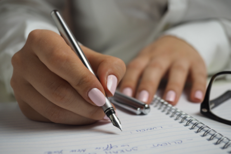 A woman's hands holding a pen and writing in a notebook